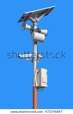 CCTV camera and speakers pole isolated on blue background.