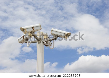 CCTV Camera in cloudy blue sky background. - stock photo