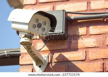 CCTV Camera on brick wall - stock photo