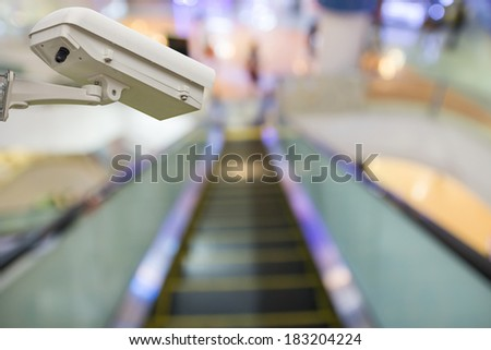 CCTV Camera Operating inside a station or department store - stock photo