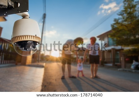 CCTV Camera Operating with family in background of village - stock photo