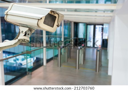 CCTV camera or surveillance operating in building entrance - stock photo