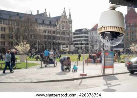 CCTV camera or surveillance operating in city - stock photo