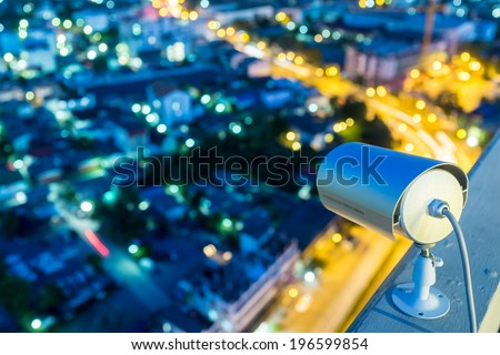 CCTV Camera or surveillance Operating in night time with city blur in background - stock photo