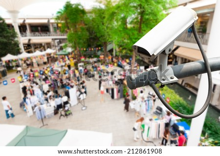 CCTV camera or surveillance operating with crowded people in background - stock photo