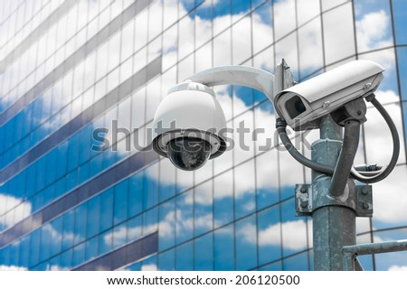 CCTV camera or surveillance operating with glass building in background - stock photo