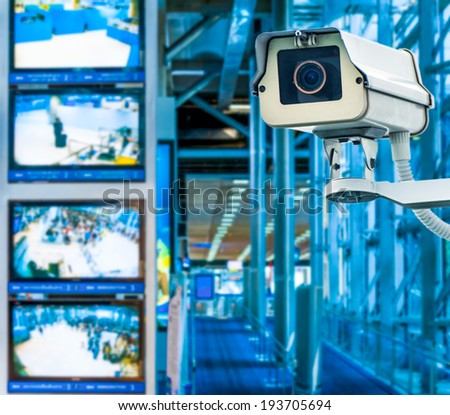 CCTV Camera or surveillance operating with monitor in background - stock photo