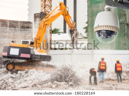 CCTV camera watching an excavator and workers working on a construction site. - stock photo
