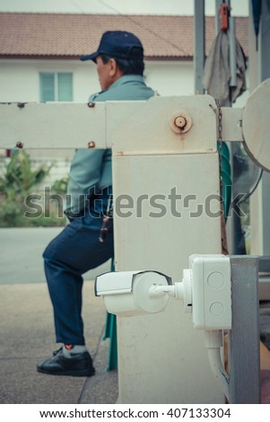 CCTV in village defocus on security man sitting background , process in vintage style - stock photo