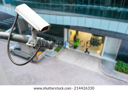 CCTV or surveillance operating on building entrance - stock photo