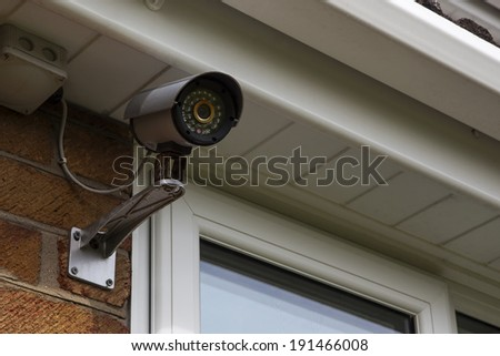 CCTV security camera for home protection, privacy, security against crime & surveillance, mounted on house exterior wall. - stock photo