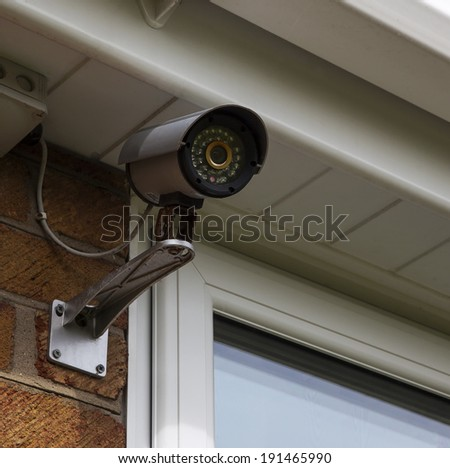 CCTV security camera for home security & surveillance, for privacy and protection against crime, mounted on house wall. - stock photo