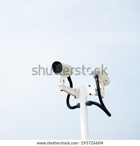 CCTV security camera isolated on sky background. - stock photo