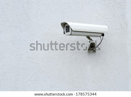 CCTV security camera on a gray the wall - stock photo