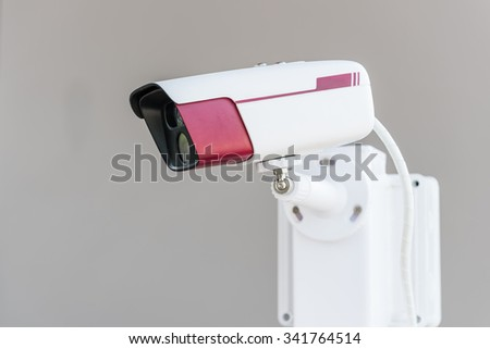 CCTV security camera on grey background - stock photo