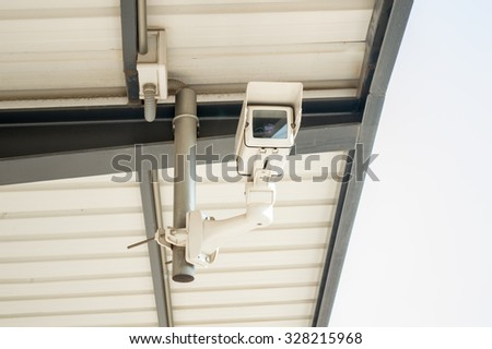 CCTV security camera on the roof of the station platform - stock photo