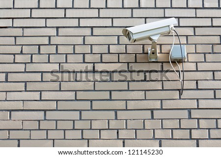 CCTV Security Camera. Security camera mounted on the outdoors brick wall. - stock photo