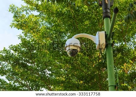 CCTV surveillance camera on top of building. - stock photo