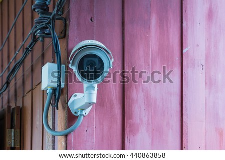 CCTV surveillance camera on  wall background for safety concept. - stock photo