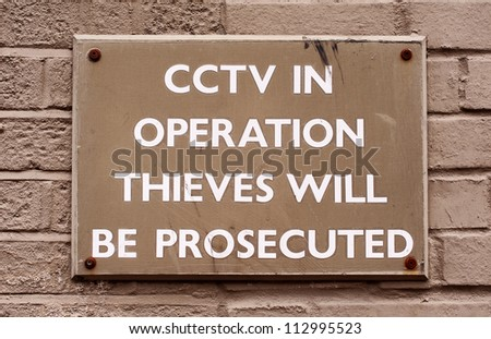 CCTV warning sign used a method of crime prevention.  The words are painted in white and on a painted wooded square block that has been screwed onto a brick wall
