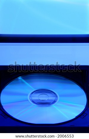 CD rom in open drive of computer with a blue tone - stock photo