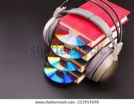 Cd sticks out from red books with headphones on it - stock photo
