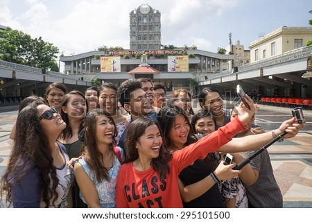 Cebu, Philippines - May 23, 2015 : A group of unidentified cheerful friends taking selfie at famous monument in Cebu City, Philippines. - stock photo