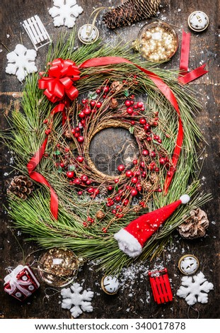 Cedar Christmas wreath with winter berries , ribbon and holiday decorations on rustic wooden background, top view. - stock photo