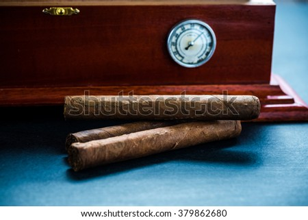 Cedar humidor and cigars, low light on dark background - stock photo