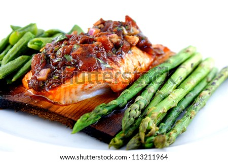 Cedar planked salmon served under roasted tomato vinaigrette and accompanied by sugar snap peas and blistered asparagus. - stock photo