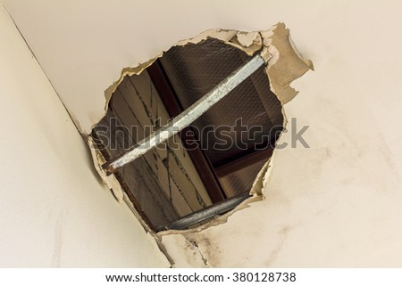 Ceiling panels damaged as a huge hole in the roof from rainwater leakage. - stock photo