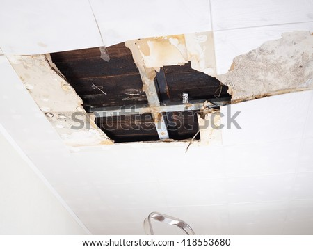 Ceiling panels damaged  huge hole in roof from rainwater leakage.Water damaged ceiling . - stock photo
