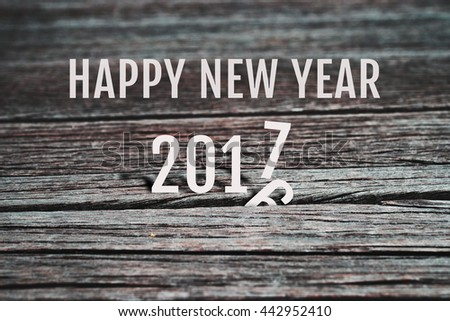 Celebrate Happy New Year 2017, coming to replace 2016. Abstract background for new year 2017 celebration, alphabet number paper character on grunge retro wood panel background, vintage style.