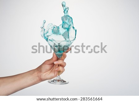 celebrate the holiday background - hand with Martini cocktail making toast - wonderful splash - stock photo