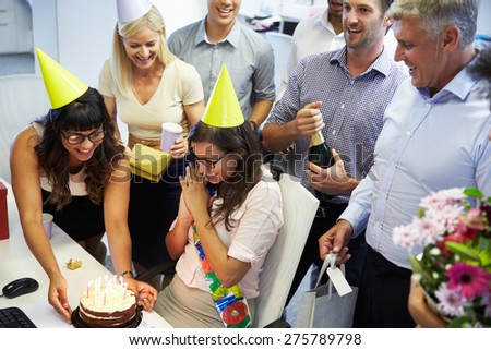 Celebrating a colleague's birthday in the office - stock photo