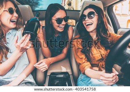 Celebrating a great day. Three beautiful young cheerful women looking at each other with smile and holding champagne bottle while sitting in car - stock photo