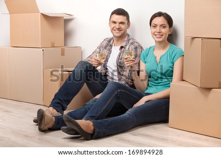 Celebrating a new dwelling. Beautiful young loving couple sitting on the floor and holding glasses with wine while cardboard boxes laying around them  - stock photo