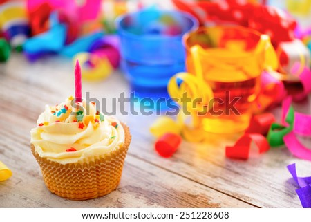 Celebrating a special day. Side view image of a cupcake with multicolored confetti as a frame and bright glasses on the background