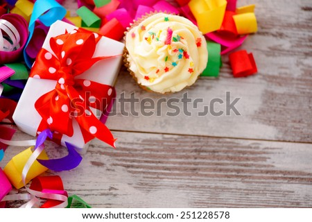 Celebrating a special day. Top view image of multicolored confetti as a frame for a gift box with red ribbon and a cupcake on wooden table with copy space - stock photo