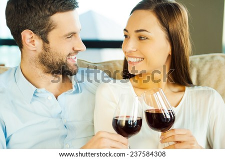 Celebrating anniversary. Beautiful young loving couple sitting close to each other and drinking red wine - stock photo