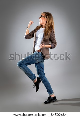 Celebrating cheering businesswoman isolated. Funny image of happy young business woman in full length. High angle view with near fisheye effect. isolated on gray background. - stock photo