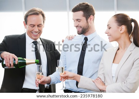 Celebrating good contract. Happy mature businessman pouring champagne while man and woman in formalwear standing close to him and holding champagne flutes  - stock photo