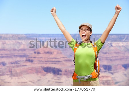 Celebrating happy hiker woman Grand Canyon cheering with arms raised up in winning gesture enjoying the beautiful landscape. Hiking girl wearing backpack during summer in, Arizona, United States. - stock photo