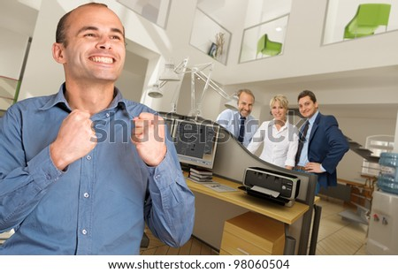 Celebrating man in a modern busy office - stock photo
