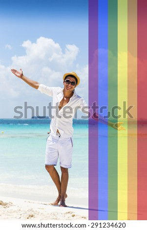 Celebrating marriage equality, handsome man at the beach with the LGBT flag overlapped on a side with medium opacity.  - stock photo
