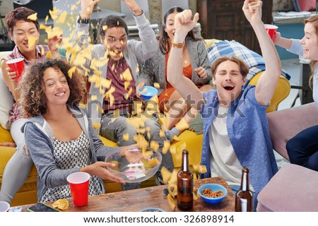 Celebrating multi racial group of sports fans student friends sharing snacks celebrating winning goal for season drinking beer throwing chips celebrating sport match - stock photo
