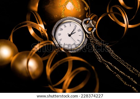 Celebrating New Year Eve concept with vintage watch, baubles and decoration ribbon on black (toned image)