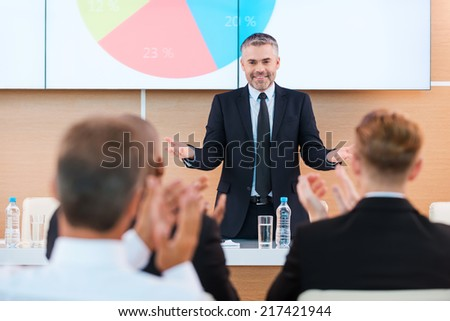 Celebrating success. Confident mature man in formalwear gesturing and smiling while making presentation in conference hall with people applauding on the foreground