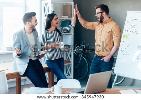 Celebrating success. Happy young man standing near whiteboard in office and giving high five to his colleagues - stock photo