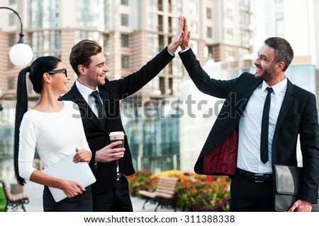 Celebrating success. Two happy young businessmen giving high five while their female colleague holding digital tablet and smiling  - stock photo